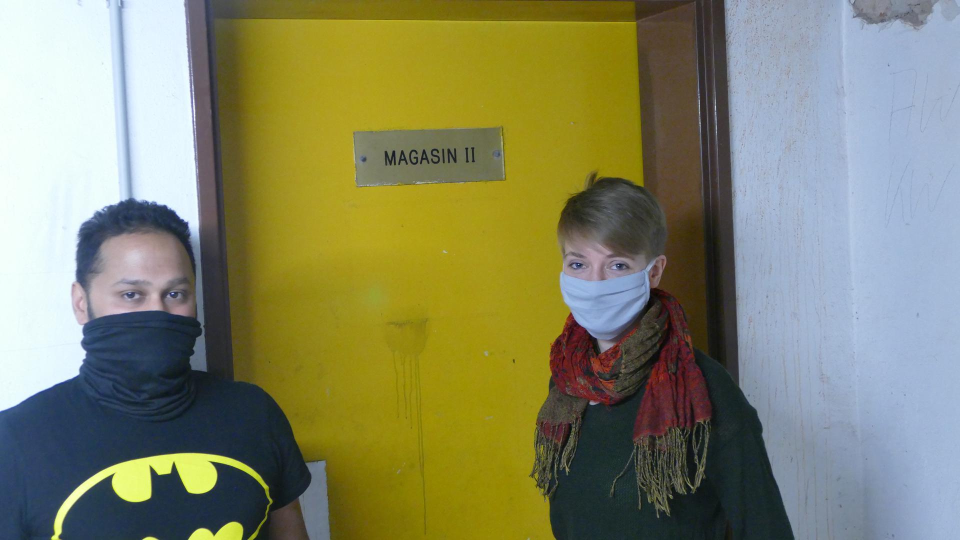 Zwei Leute mit Masken vor Tür
