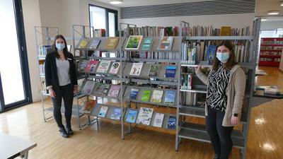 Zwei Frauen an Buchregal