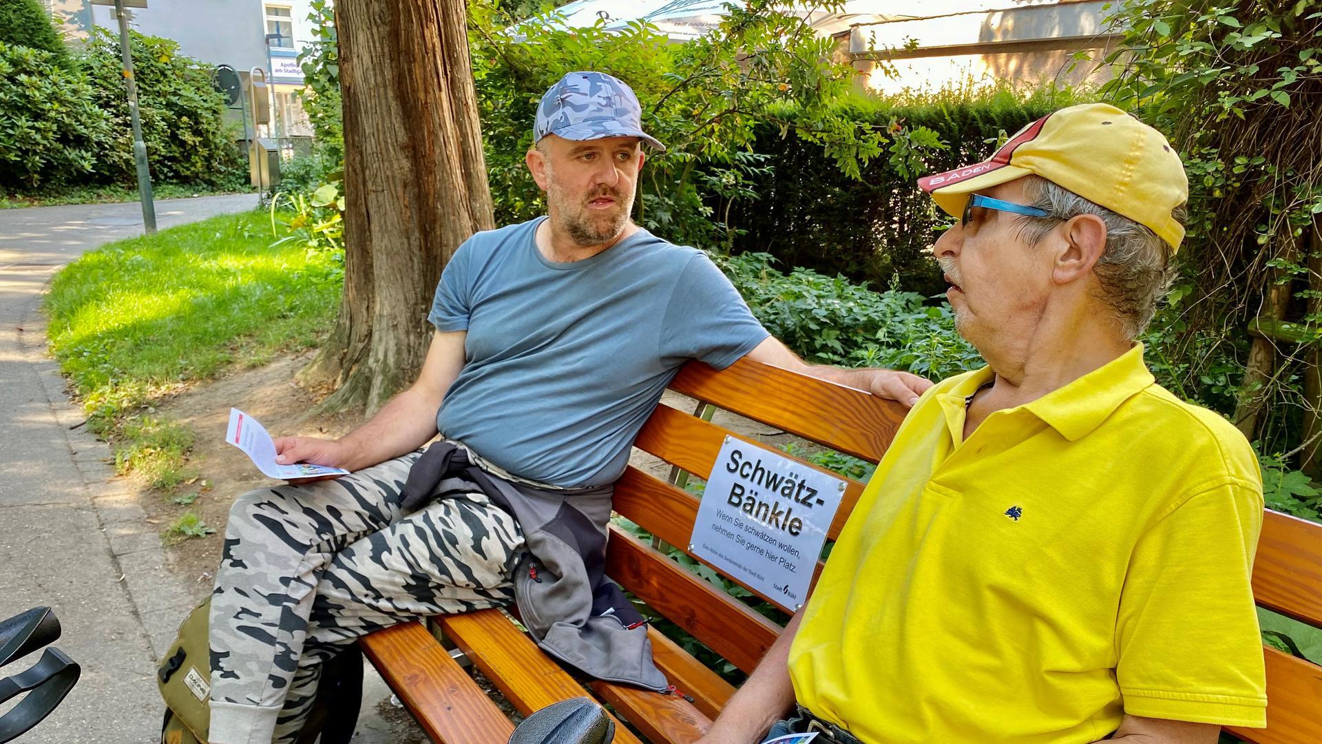 Zwei Männer sitzen auf einer Parkbank.