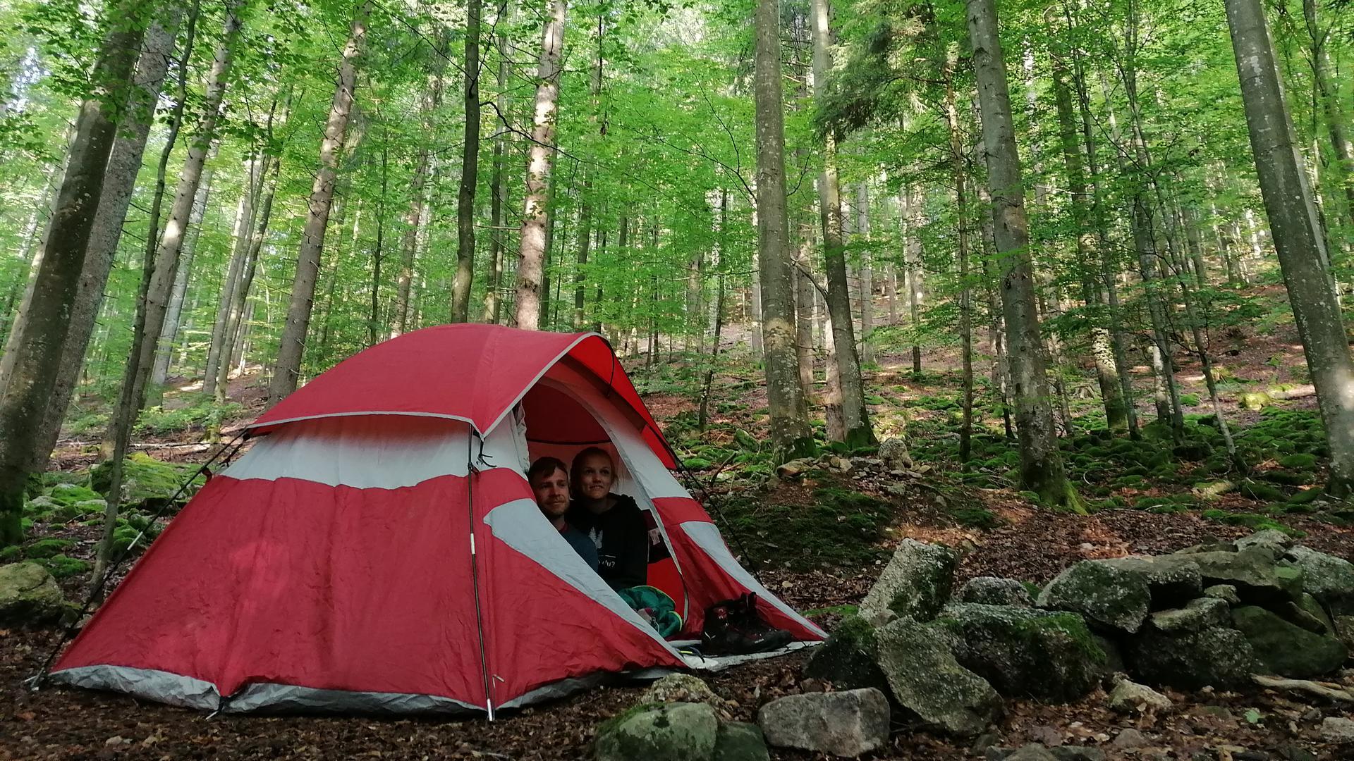 Zelt im Trekkingcamp Grimbach, aus dem zwei Personen herausschauen.