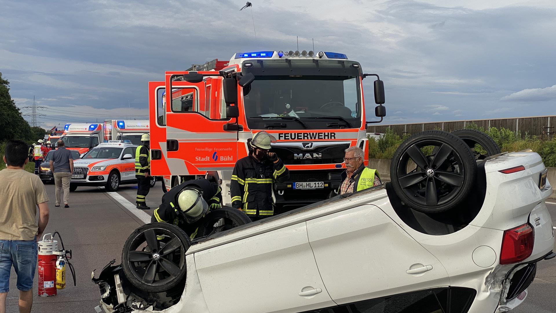 Ein weißes Auto liegt auf dem Dach. Im Hintergrund Feuerwehrfahrzeuge und Rettungswagen.