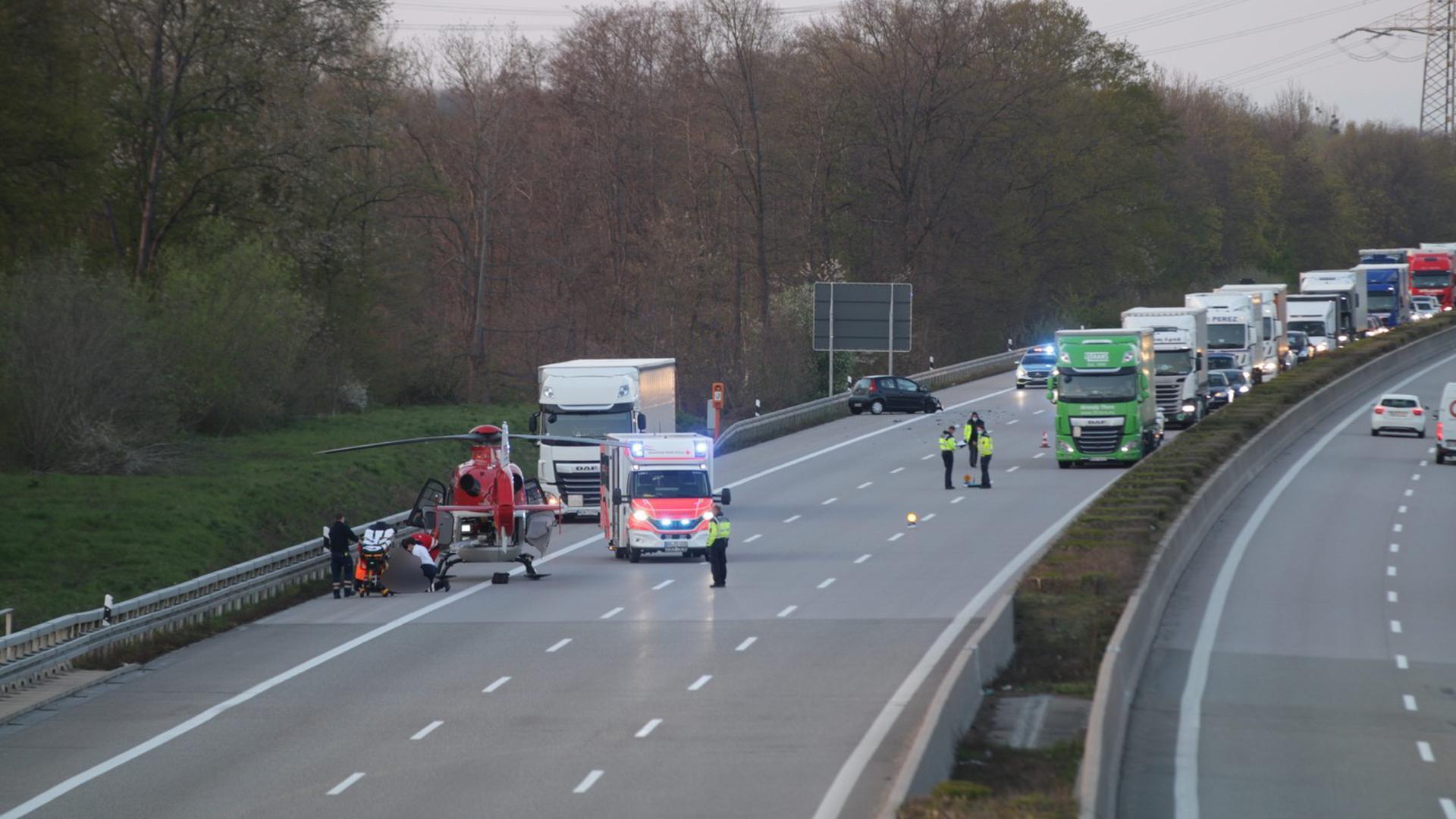 Die A5 bei Bühl. Im Vordergrund ein Rettungshubschrauber und ein Krankenwagen mit Blaulicht vor einem weißen Lkw auf dem Seitenstreifen. Rechts im Stau stehende Lkw.