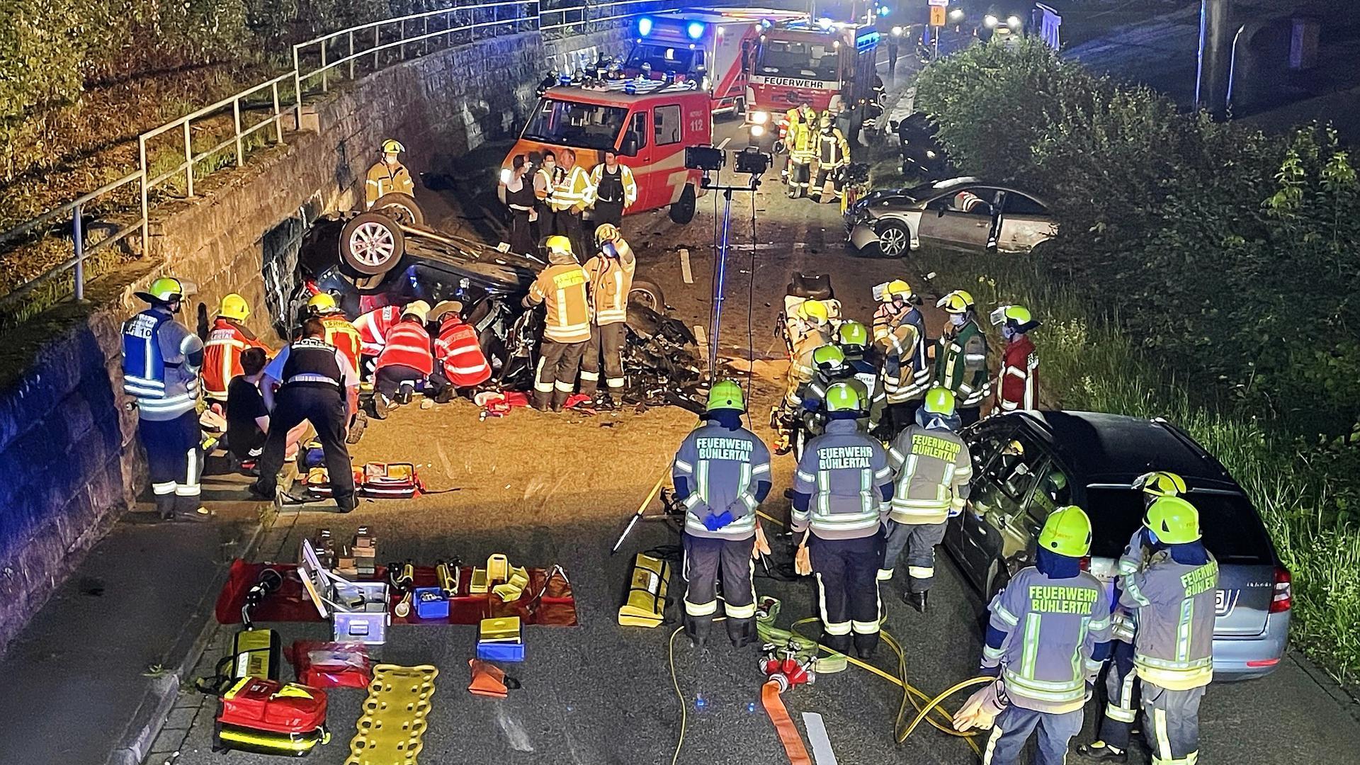 Ein Auto liegt auf der Straße auf dem Dach, zwei weitere sind im Grünstreifen. Zahlreiche Rettungskräfte von Feuerwehr und Rettungsdienst sind im Einsatz.