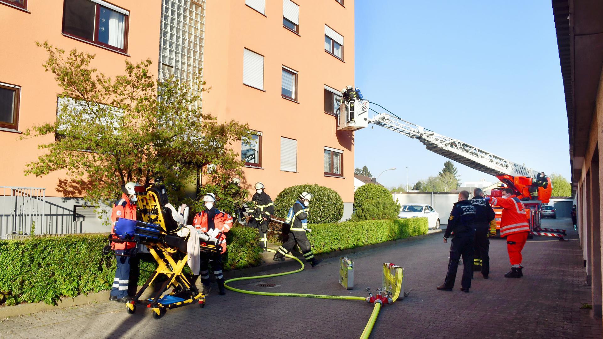 Mehrere Feuerwehrleute mit der Drehleiter am Fenster. Im Vordergrund weitere Einsatzkräfte von Polizei, Rettungsidenst und Feuerwehr.