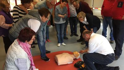 Ein Mann zeigt an einer Puppe den richtigen Einsatz eines Defibrillators. Drumherum stehen Frauen und Männer, die an dieser Schulung teilnehmen.