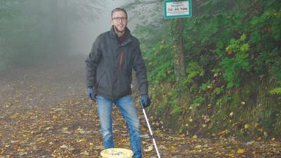 Mann mit Mülleimer im Nebel