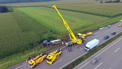 Luftaufnahme des umgekippten Sattelzugs. Mehrere Einsatzfahrzeuge zur Bergung vor Ort.