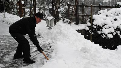 Mann beim Schneeschippen