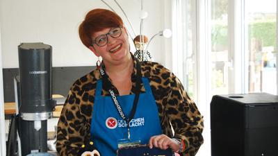 """Lily van Daalen  mit Glücksbiene und selbstgenähtem Schürzenaufsetzer, den sie in der ZDF-Sendung """"Küchenschlacht"""" als Topflappen nutzte."""