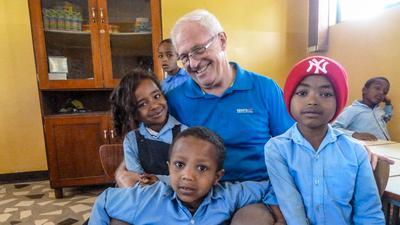 Ein Mann mit mehreren Kindern auf dem Arm.
