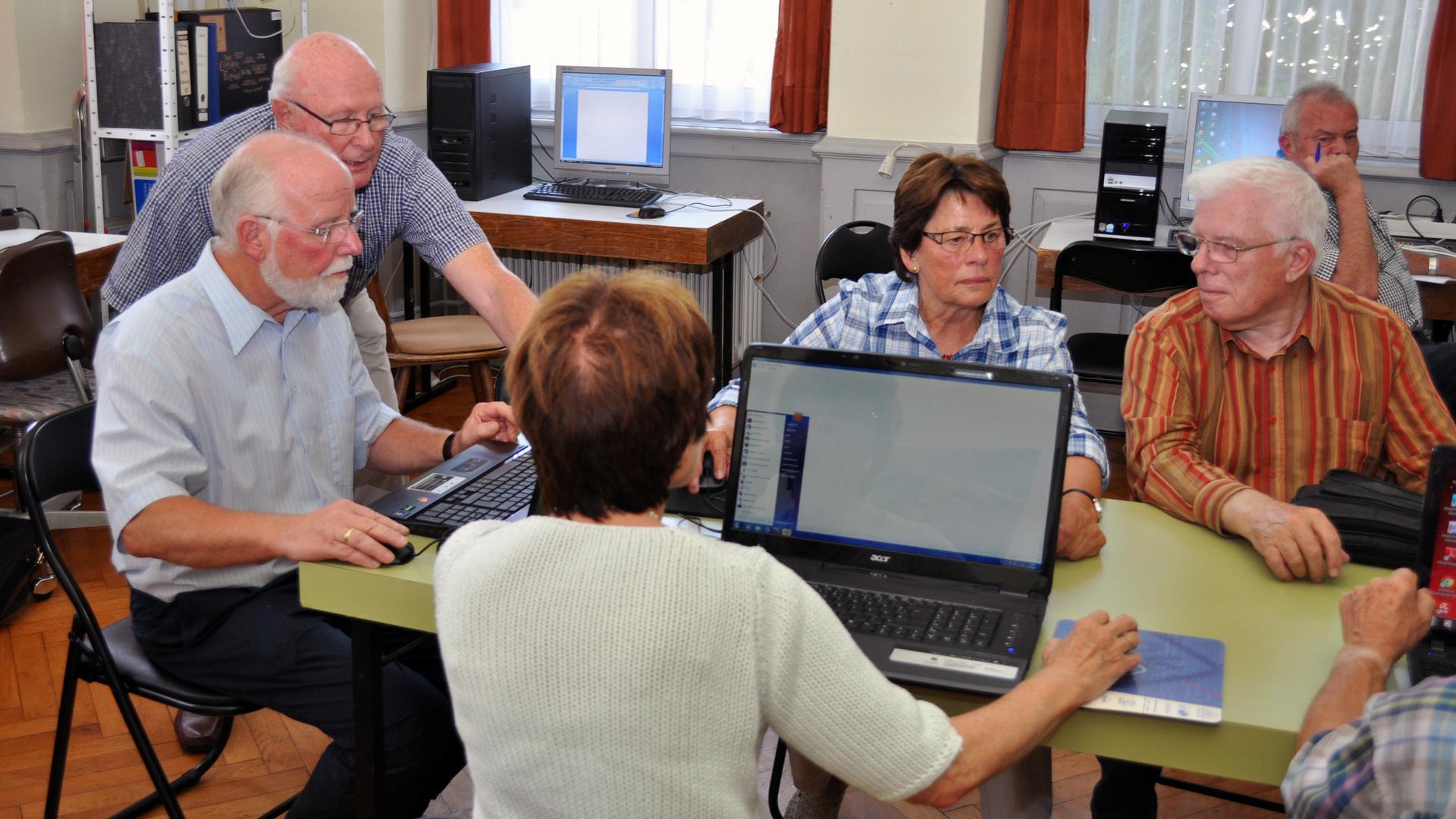 Senioren in einer Gruppe an Tischen mit Computern