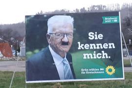 Landtagswahlkampf-Plakat der Grünen, auf dem Winfried Kretschmann mit einem aufgemalten Hitlerbart zu sehen ist.