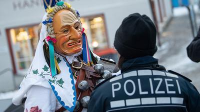 Ein Narr spricht am Fastnachtsmontag mit einer Polizeibeamtin. Aufgrund der Corona-Pandemie wurde der Narrensprung zwar offiziell abgesagt, einige Narren waren trotzdem unterwegs. Der Rottweiler Narrensprung ist einer der Höhepunkte in der schwäbisch-alemannischen Fastnacht und einer der traditionellen Umzüge im Südwesten. +++ dpa-Bildfunk +++