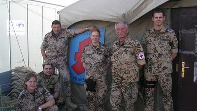 6 Personen in Uniform vor Zelt