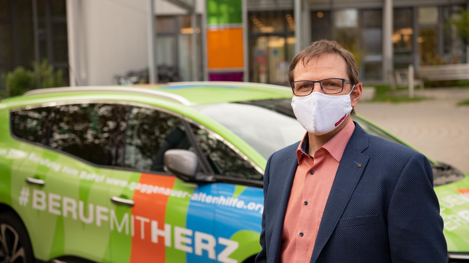 """Mann mit Maske vor Auto mit Aufschrift """"Beruf mit Herz"""""""