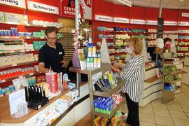 Apotheker bedient Kundin mit gestreifter Bluse