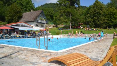 Eine Sonnenliege in einem Schwimmbad mit vielen Menschen.