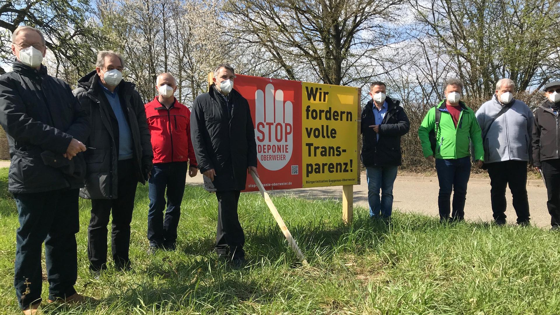 "Männergruppe neben Schild ""Transparenz"""