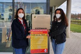 Zwei junge Frau zeigen vor dem Landratsamt in Rastatt ein Plakat mit Fragen an den Abfallwirtschaftsbetrieb zum Thema Sickerwasser auf der Deponie Hintere Dollert