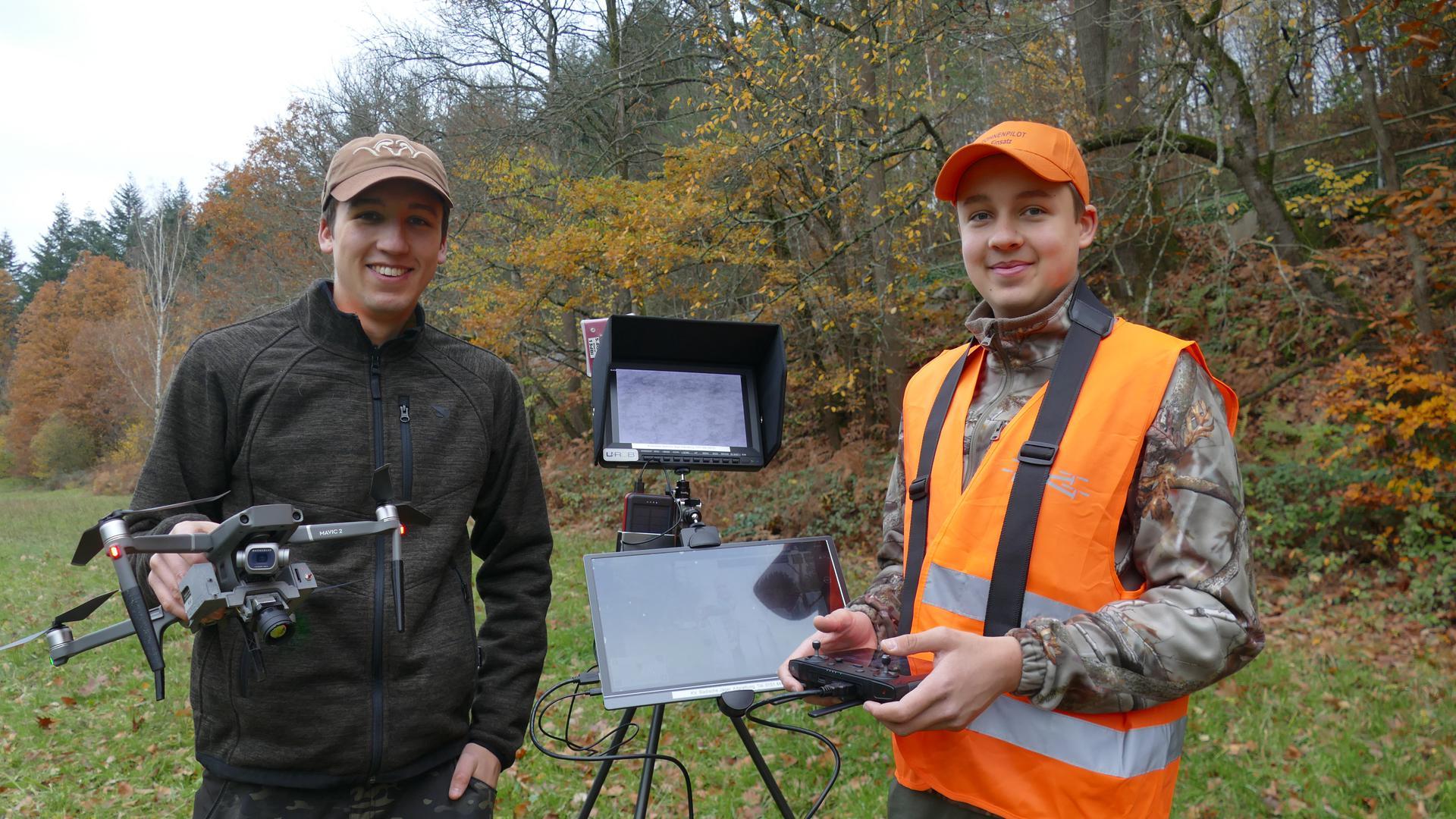 zwei junge Männer mit Drohne und Stativ