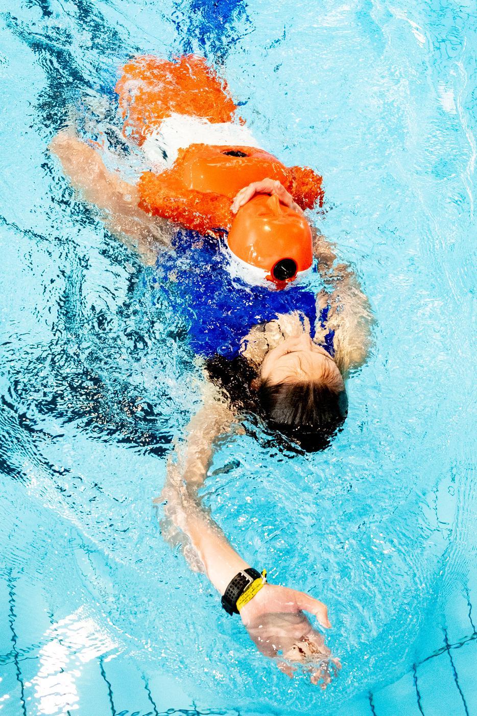 Eine Frau schwimmt und hält eine Rettungspuppe im Arm.