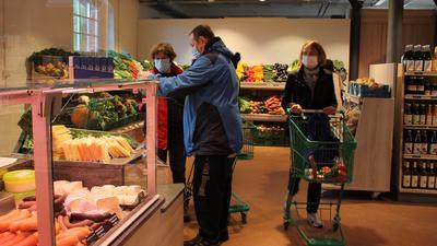 Laden mit Wursttheke, Gemüseregalen im Hintergrund und Kunden
