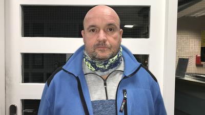 Ein Mann mit Glatze vor einer Eingangstüre
