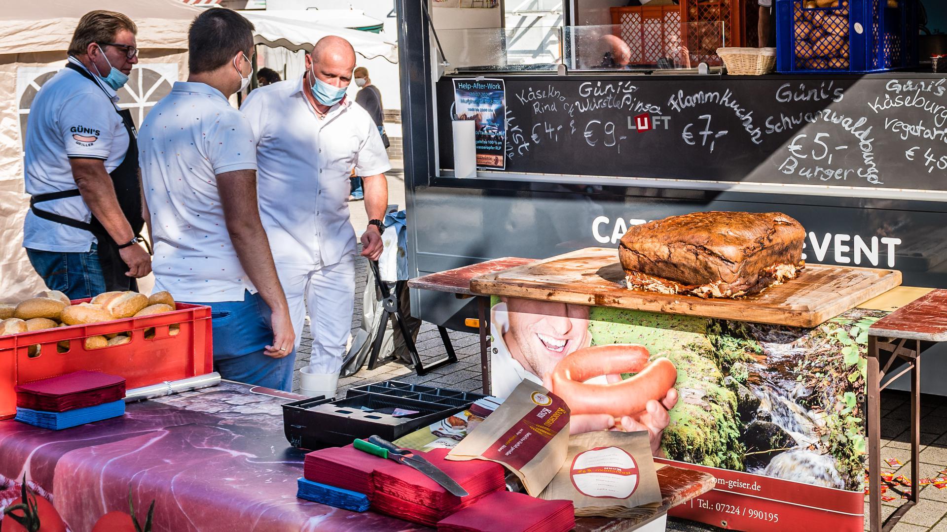 Gleich geht es los. Bürgermeister Christ (Mitte) bekommt noch von Steffen Geiser (ganz rechts) die Schürze umgebunden, und darf den Fleischkäse anschneiden.