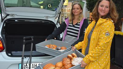 Zwei Frauen beim Einladen von Backwaren in ein Auto