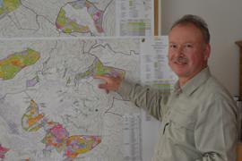 Forstbezirksleiter Markus Krebs steht in seinem Büro in Bad Rotenfels vor einer Wandkarte.
