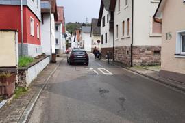 Pkw und Fußgänger auf einer Straße in Hörden