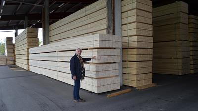 Hördener Holzwerke: Seniorchef Gerhard Strobel an gelagerten Holzstapeln