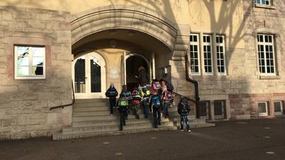 Vor dem Eingang der Hans-Thoma-Schule steht eine Gruppe von Schülern