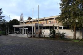 Blick auf alte Sporthalle rechts Baum