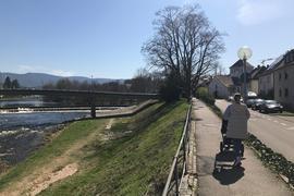 links Fluss und Brücke, rechts Fußgängerin