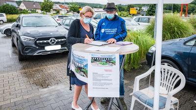 Zwei Personen an einem Stehtisch, Unterschriftenaktion