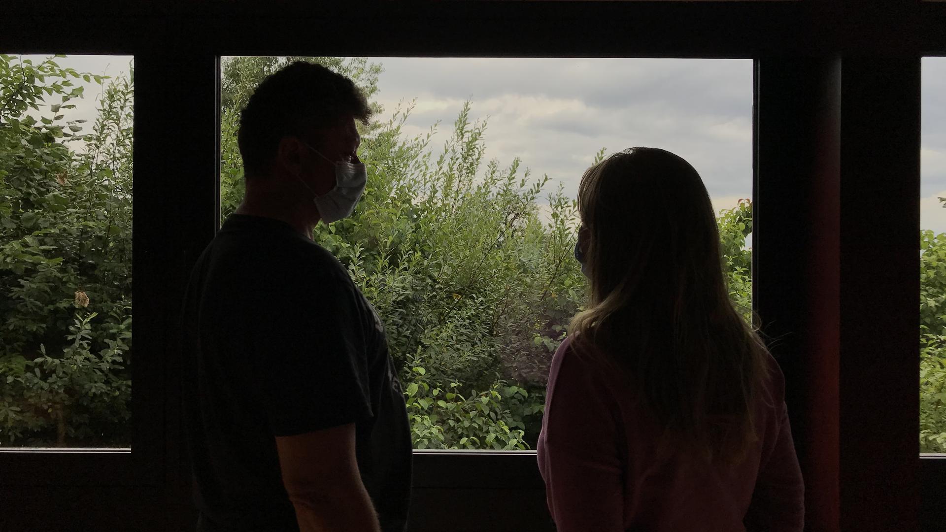 zwei Silhouetten vor einem Fenster