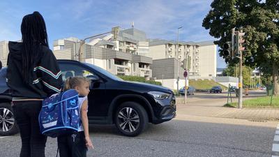 Ein Schulkind steht mit seiner Mama an einer Kreuzung