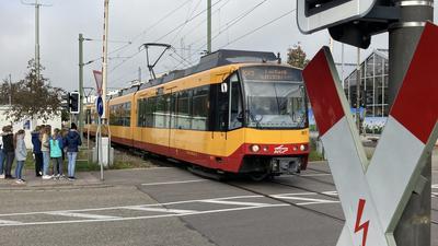 Eine Bahn fährt an einem Übergang, obwohl die Schranken offen sind.