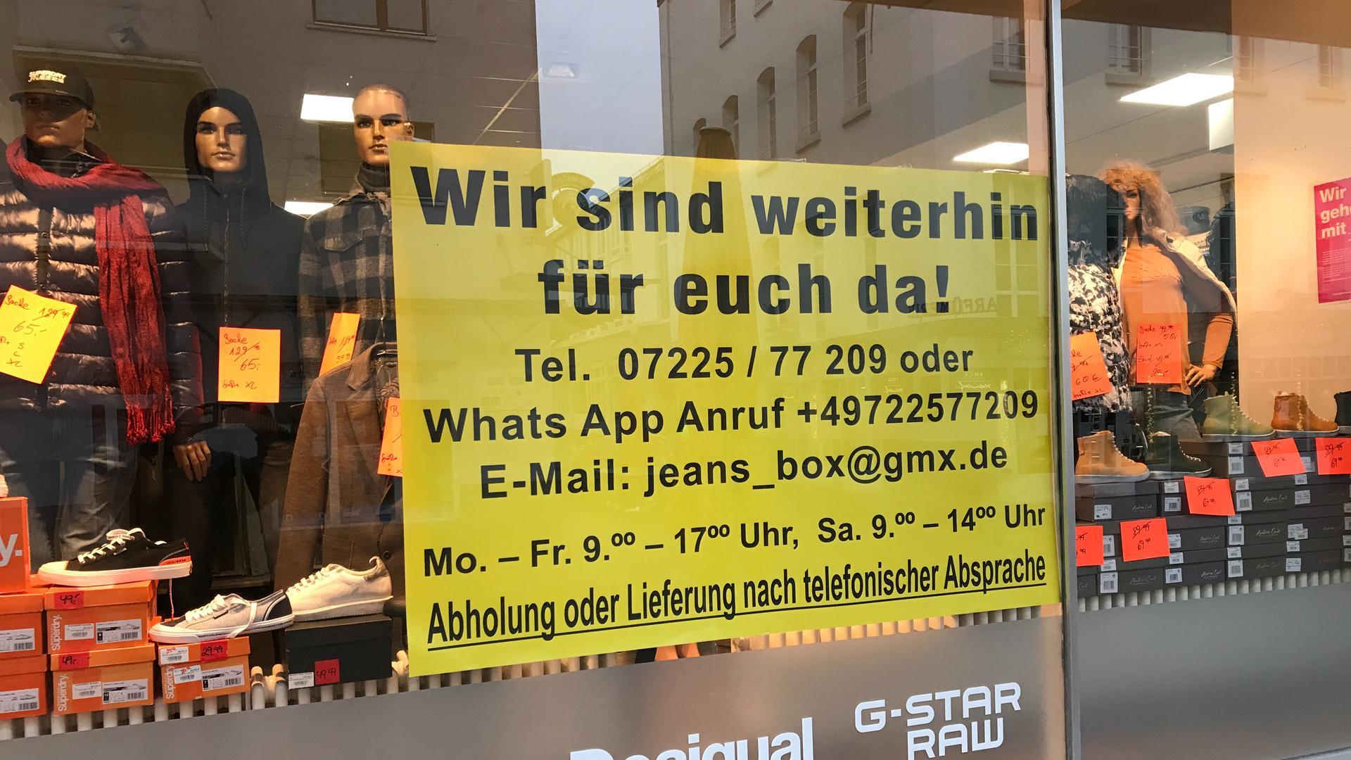"""Im Schaufenster ihres Ladens """"Jeans-Moden"""" in der Gaggenauer Fußgängerzone weist Melitta Strack auf die Möglichkeit hin, Waren zu bestellen und abzuholen."""