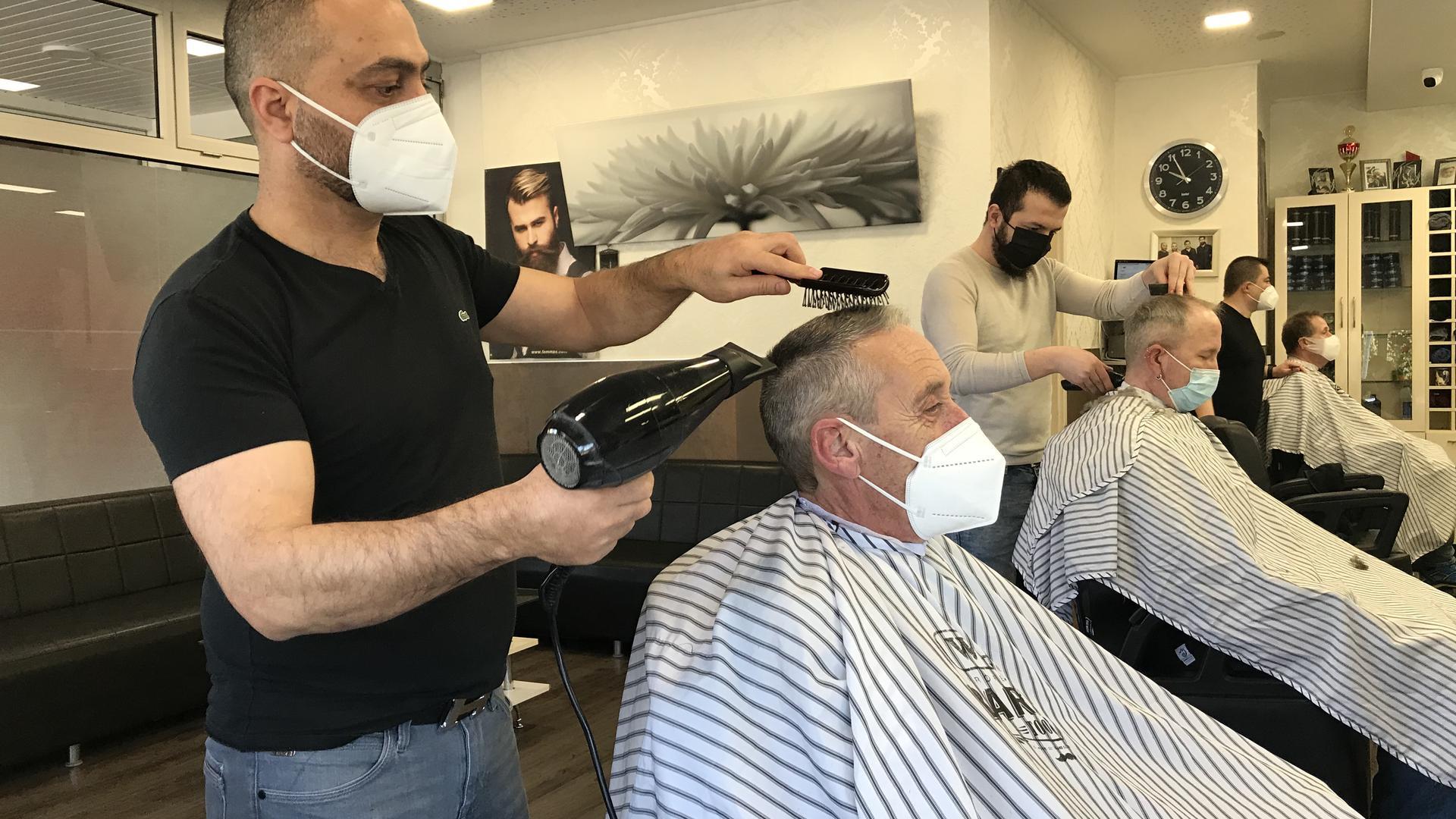 Ein Friseur schneidet einem Mann die Haare.