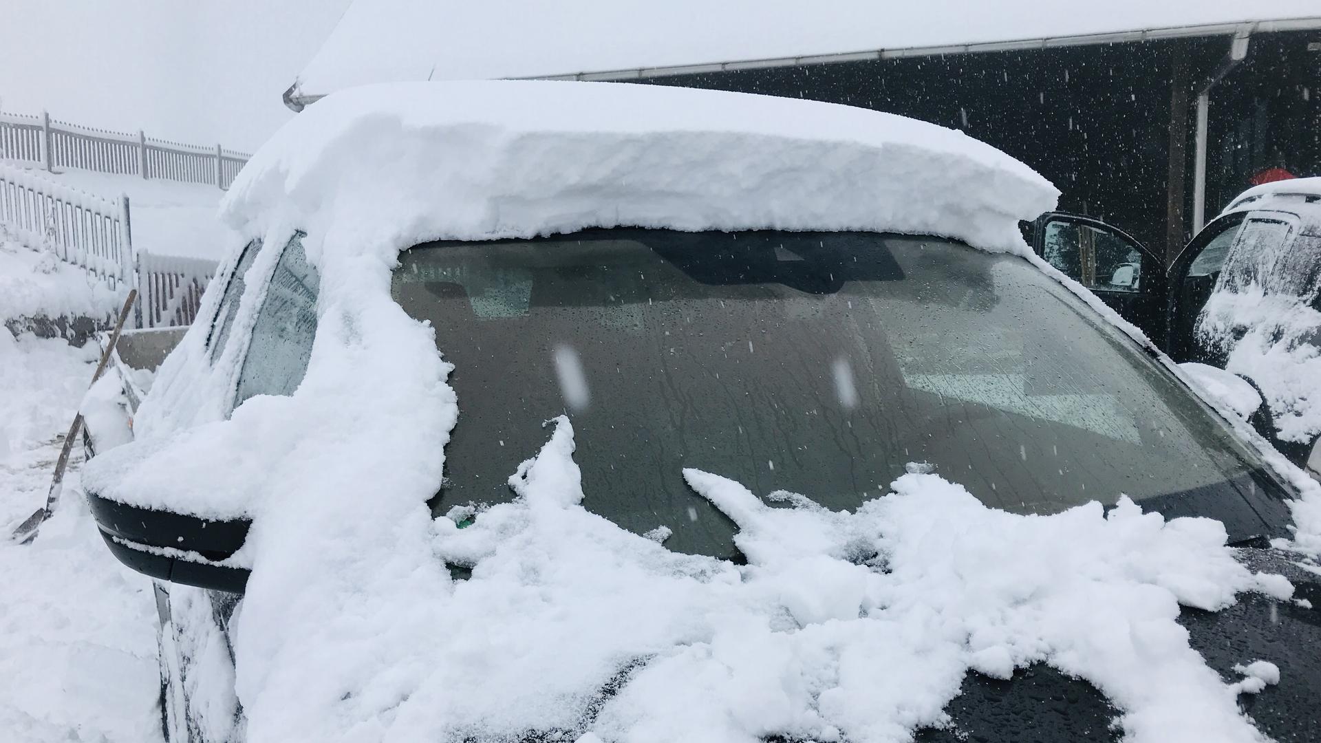 Die Frontscheibe eines Autos in Gernsbach-Kaltenbronn ist vom Schnee befreit. Auf dem Wagendach liegt der Schnee dagegen noch gut über zehn Zentimeter hoch.