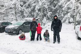 Eine Familie mit drei Kindern steht mit Rodeln auf dem schneebedeckten Parkplatz bei Kaltenbronn