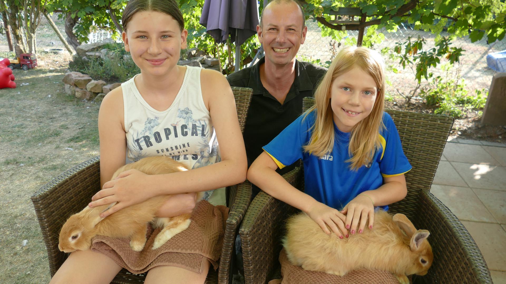 Kleintierzüchter Martin Moser, seine ältere Tochter Annalena und Patenkind Clara. Die Fuchs-Kaninchen, die die Mädchen auf dem Schoß haben, gelten als extrem gefährdete Rasse.