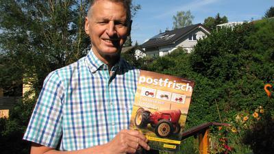 """Ein Mann mit einer Ausgabe der Zeitschrift """"postfrisch"""""""