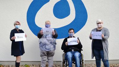 """Vor einer Wand mit dem blauen Logo der Lebenshilfe zeigen vier Personen Schilder mit dem Hinweis """"Büro für leichte Sprache"""""""