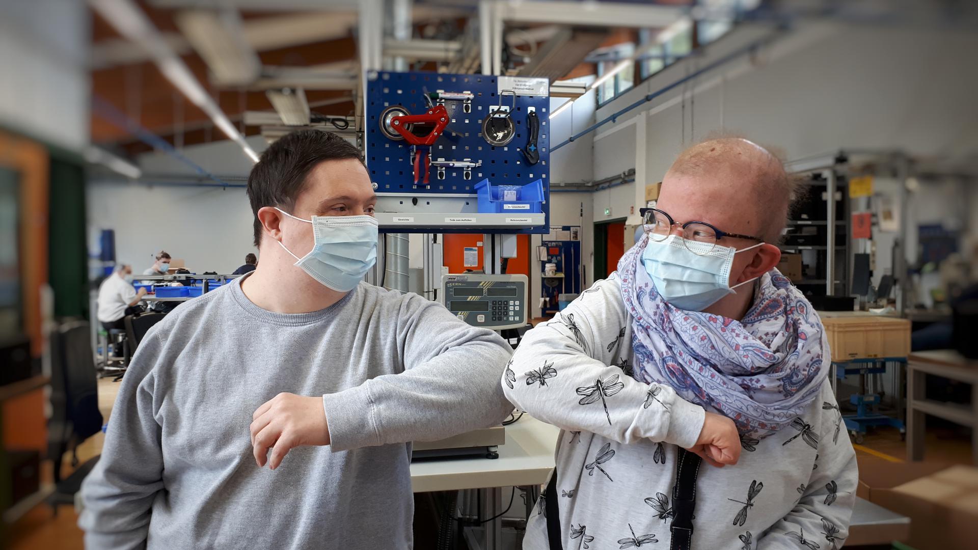 2 Personen mit Mundschutz in Werkstatt
