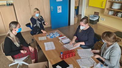 Frauengruppe mit Masken am Tisch