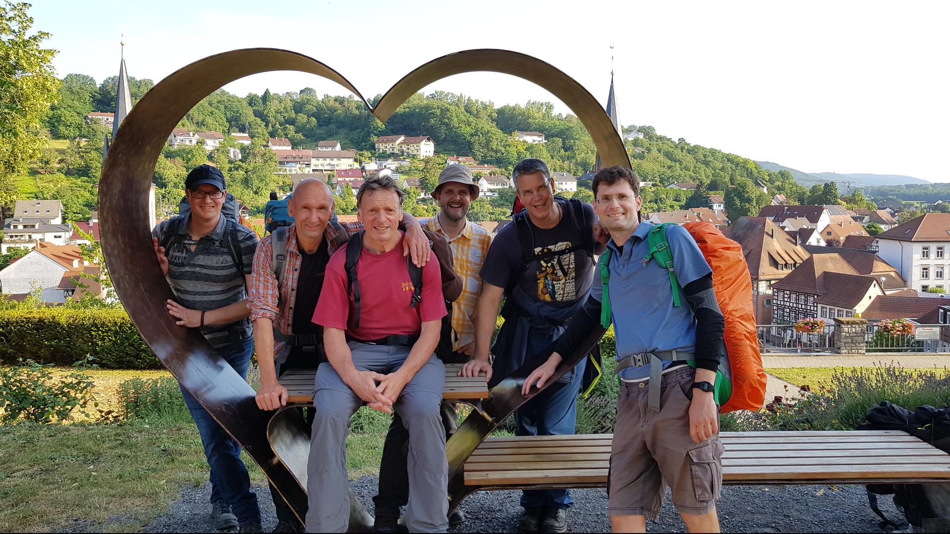 Sechs Wanderer an einem Metallherz mit Bank und Tisch in Weingarten