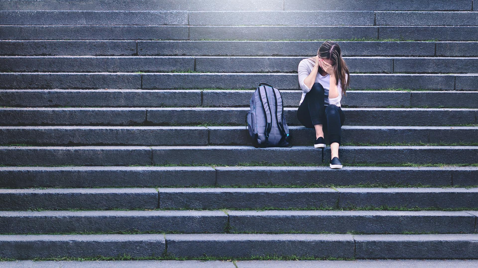 Bullying, discrimination or stress concept. Sad teenager crying in school yard. Upset young female student having anxiety. Upset victim of abuse or harassment sitting on stairs outdoors with backbag.